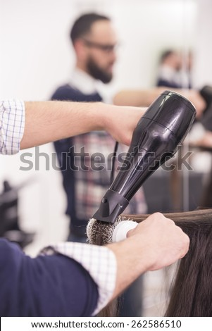 Close-up hairdresser blow dry for client hair in hairdressing salon. - stock photo