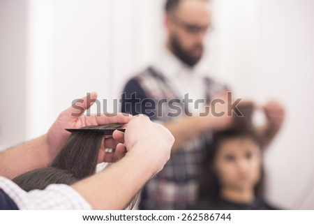 Close-up hairdresser making a haircut for a client in salon. Blurred background. - stock photo