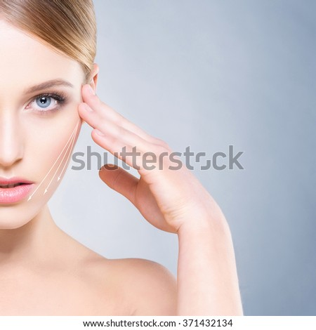 Close-up half face portrait of beautiful, young woman over navy background. Face lifting concept. - stock photo