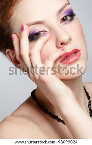close-up half-face portrait of young beautiful woman with violet eye shadow and manicured hand - stock photo