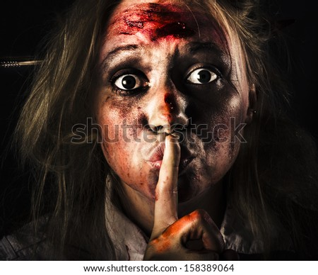 Close-up halloween portrait of a scary zombie horror face gesturing silence at the dead of night with bloody terror - stock photo