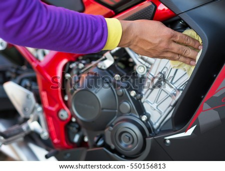 close up hand cleaning motorcycle engine