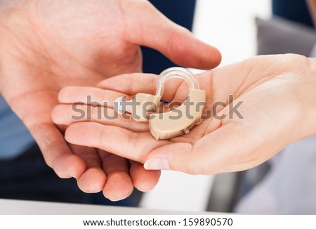 Close-up Hand Giving Hearing Aid To A Person - stock photo