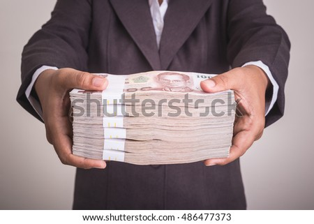 Close up hand giving Thai banknotes. Studio shot isolated on grey background