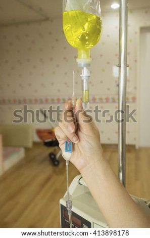 Close up hand hold needle for infusion bottle with IV solution