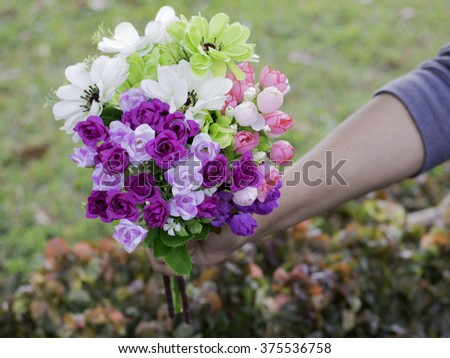 close up hand holding bouquet of artificial flower over garden background - stock photo