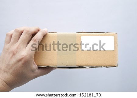 close up hand holding brown box - stock photo