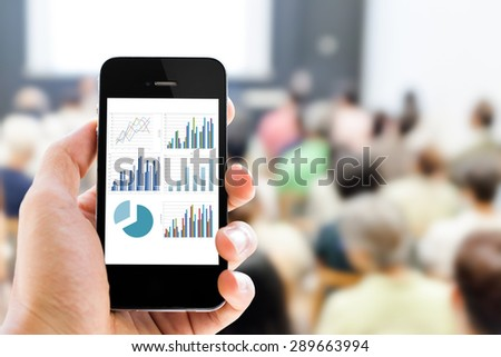 Close-up hand holding mobile phone with analyzing graph against people in business conference and presentation background  - stock photo
