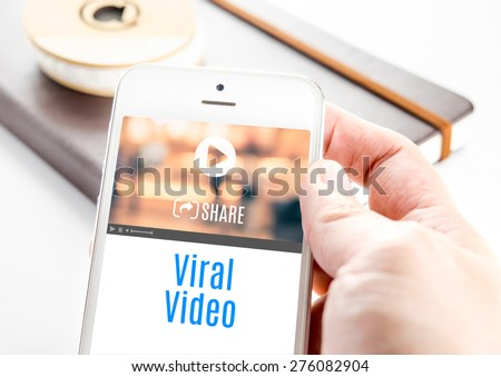 Close up hand holding smart phone with Viral Video word and icons with notebook at background, Mobile technology concept - stock photo