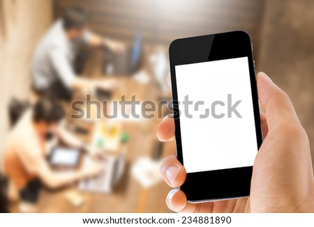 close up hand holding smartphone on blurred people using computer background   - stock photo