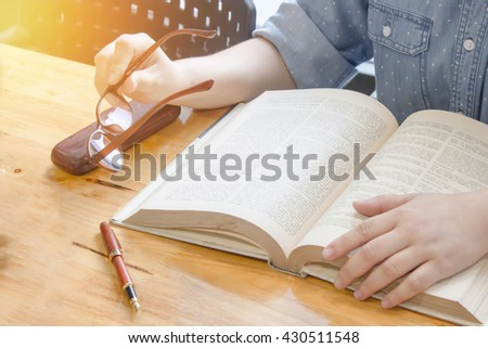 close up hand holding spectacles with reading,  rest one's eyes in library. - stock photo