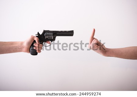 Close-up hand is holding a gun and hand with finger up. Grey background. - stock photo