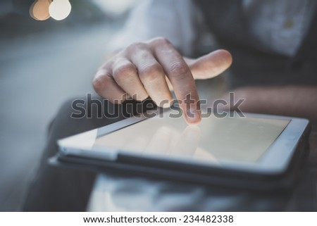 close up hand man using tablet at the bar with beer on table - stock photo