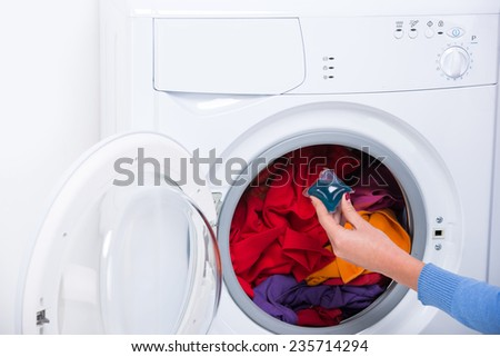 Close-up hand of a young woman is putting a detergent into washing machine.