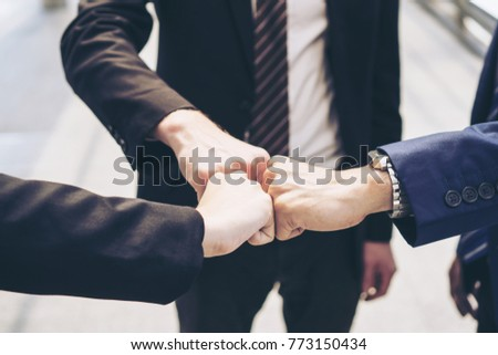close up hand of business  people bump hands finishing up meeting showing unity , business teamwork concept
