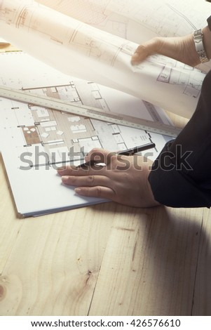 Close-up hand Of female Architect Drawing Blueprint on work space wooden table in offfice ,cross process and soft flare filter  - stock photo