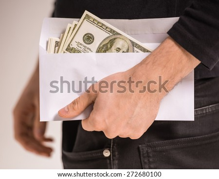 Close-up hand of man is holding envelope with money. - stock photo