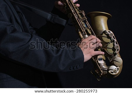 close up hand of  musician playing old alto saxophone,focus on hand saxophone player,low key image