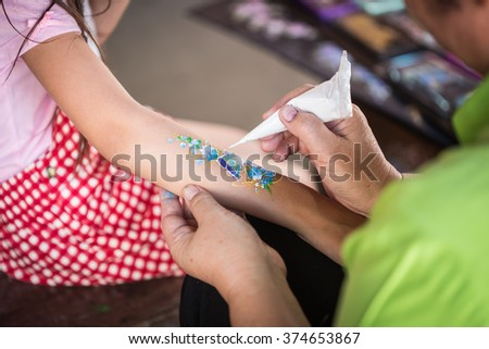 Close up hand of people making art paint on children arm