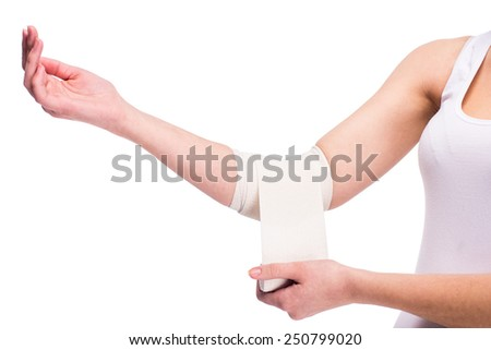 Close-up hand of woman, injured painful elbow with white bandage. - stock photo