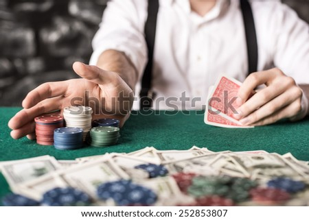 Close-up hand of young gangster man, while playing poker game, with money, chips and cards.