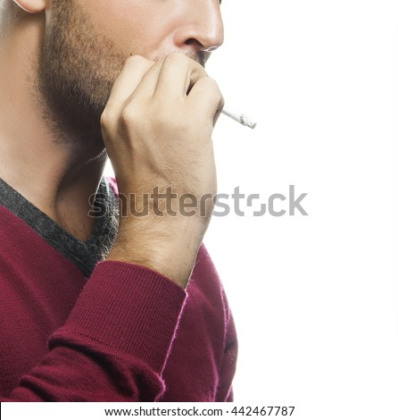 Close-up hand of young man smoking a cigarette isolated on white background. Studio portrait. Studio portrait.