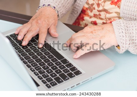 Close-up hand old woman using laptop - stock photo