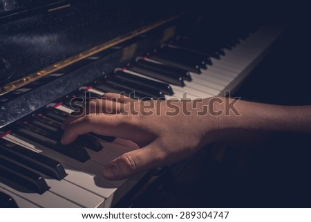 close up hand on piano in retro style