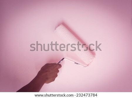 Close up hand painting pink color on the wall - stock photo
