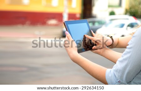 Close up hand presses on screen digital tablet. Two women hands with tablet computer and phone on the city. Closeup of women hands holding electronic tablet on a background of city streets and cars. - stock photo