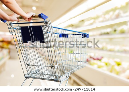 close up hand pushing shopping cart in supermarket