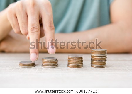 Close up hand putting money coins stack in saving money and growing, Concept save money Finance