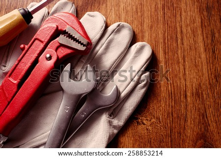 Close Up Hand Tools and Pair of Gloves on Top of a Wooden Table with Copy Space on Right Side. - stock photo