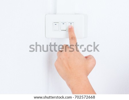 Close up hand turning on or off on light switch in white room.