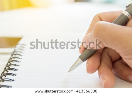 close up hand use ball pen writing on open blank  notebook focus on head of ball pen - stock photo