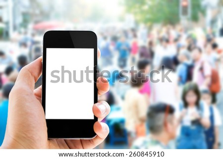 Close up hand using smart phone ,city street and people in background - stock photo