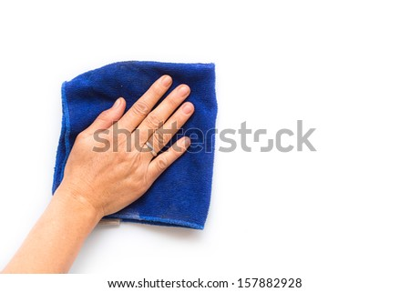Close up hand with blue cloth cleaning on white wall - stock photo