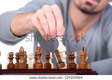 Close-up  hand with chess is making the move on the white background. - stock photo
