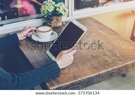 Close up hand woman using tablet in coffee shop with vintage tone. - stock photo