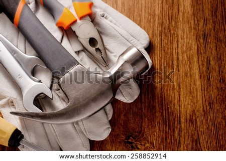 Close up Hand Working Tools Like Hammer, Wrench and Pliers on Top of White Gloves Placed on a Wooden Table with Copy Space on the Right Side