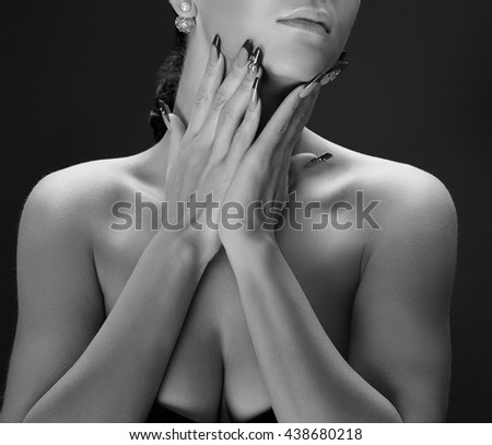 Close-up hands and shoulders of caucasian brunette woman with perfect nails. Isolated on black background. Black and white - stock photo