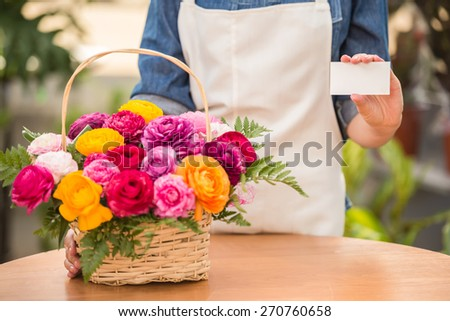 Close-up. Hands female florist holding visit card with bouquet.