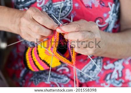 Close up hands grandmother knitting socks - stock photo