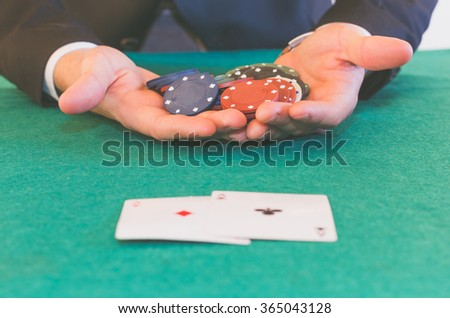 close-up hands holding chips winning with pocket of aces - poker, business, success, and lifestyle concept
