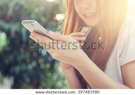 Close up hands holding credit card and using mobile smart phone outdoor, Online shopping, woman happy. - stock photo