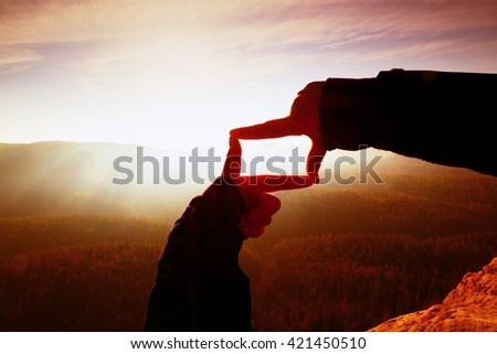 Close up hands making frame gesture. Orange misty valley bellow. Sunny spring daybreak in mountains. Red vintage style. - stock photo