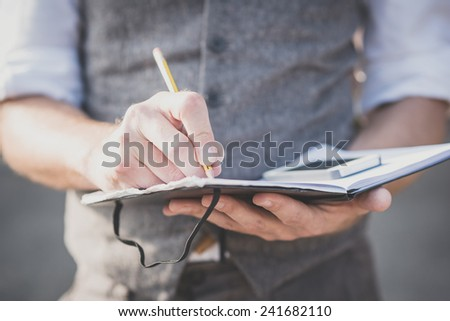 close up hands man writing on diary and smartphone outdoor - stock photo