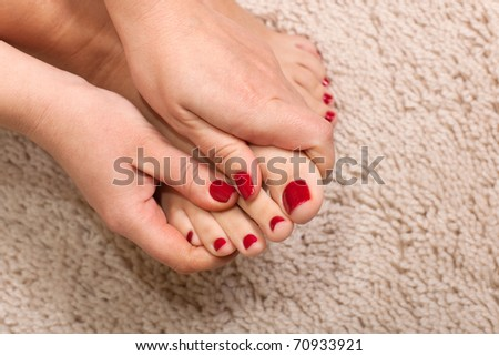 Close up hands massaging a foot at the white carpet background - stock photo