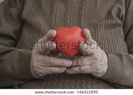 close up hands of a senior woman holding heart