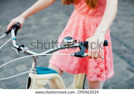 Close up hands of a young girl in pink dress, holding handbrake on vintage bicycle - stock photo